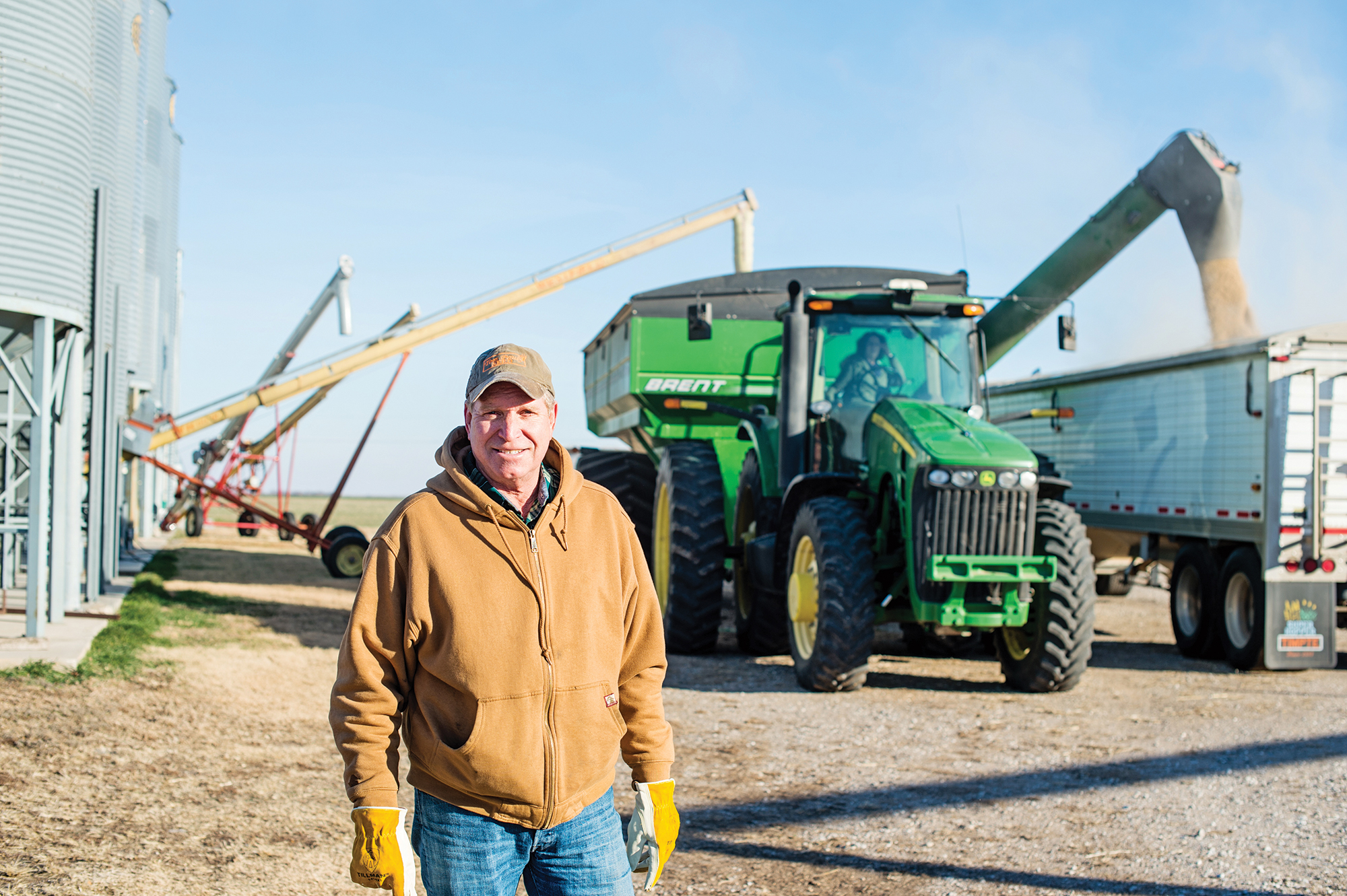 Farmer smiling in front of farm equipment