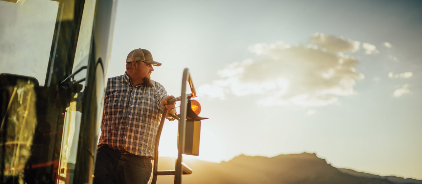 Jon Arreche looking out on a field at sunset from a piece of farm equipment