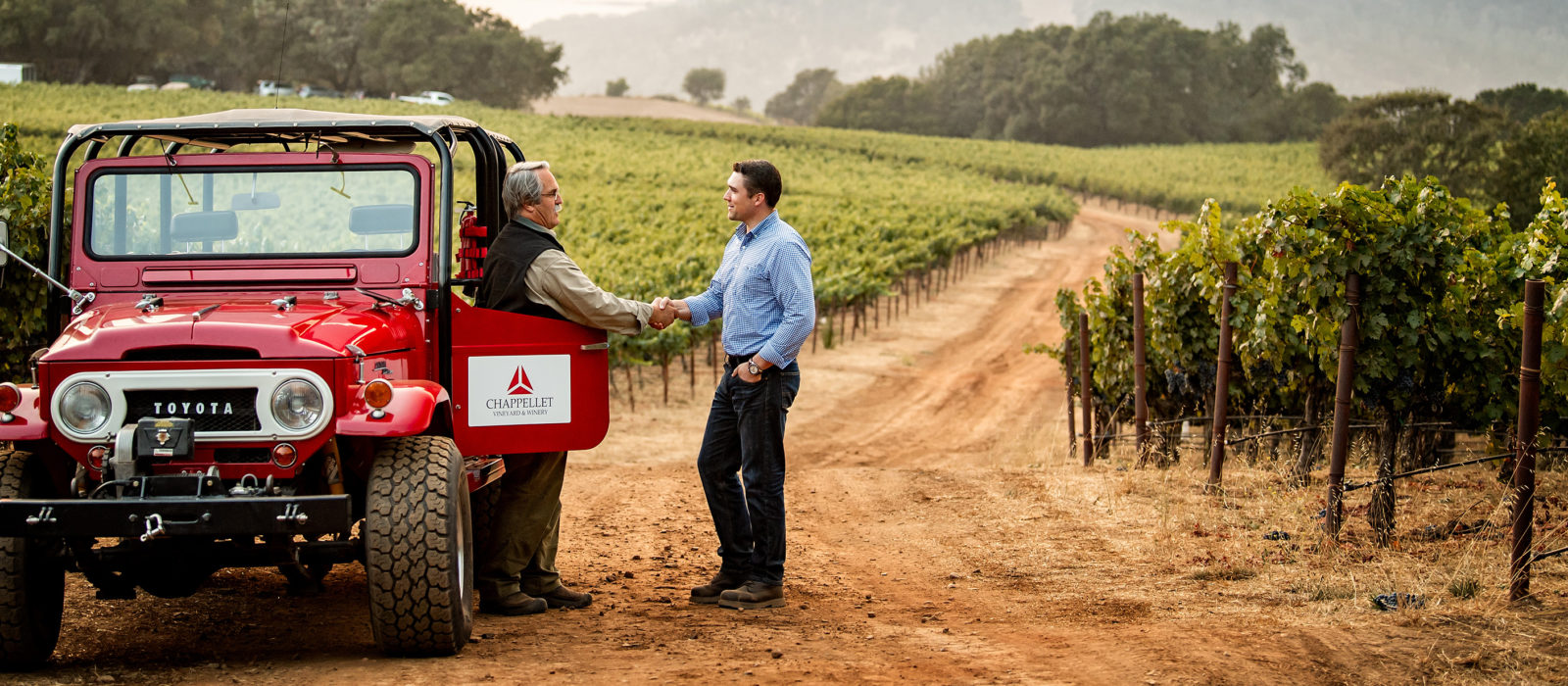 client and loan officer shaking hands in a vineyard