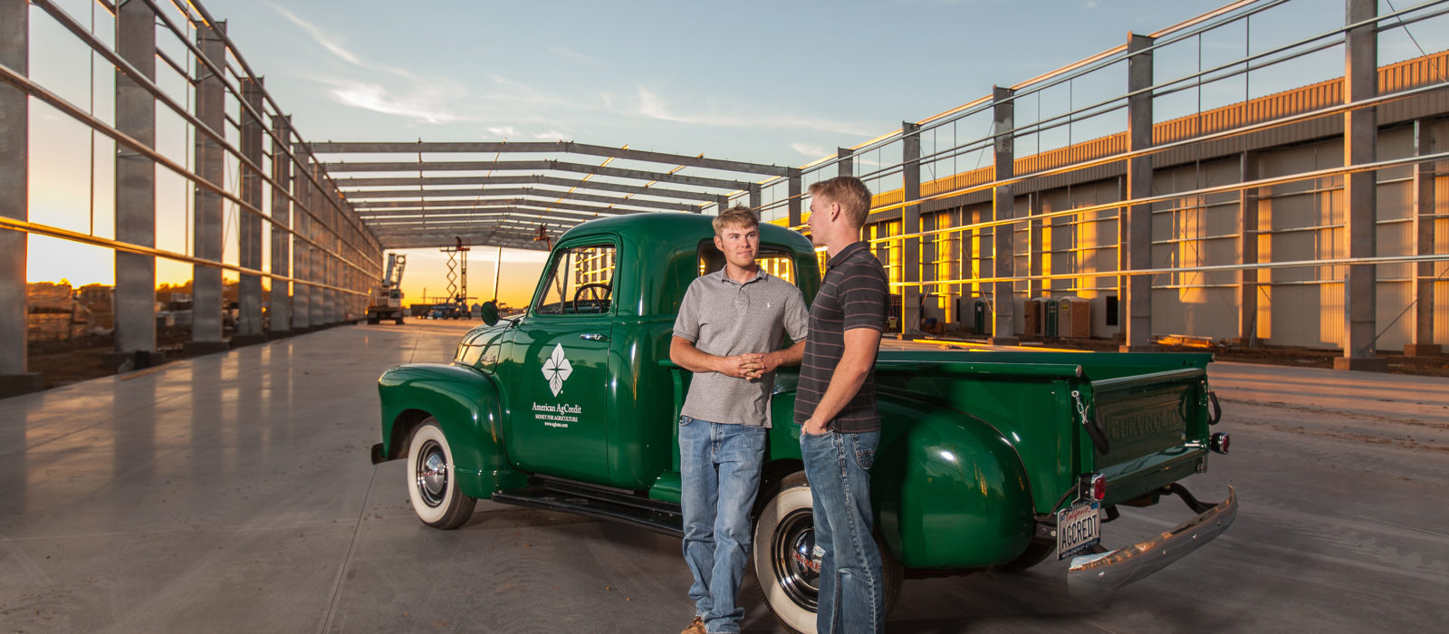 two young farmers in front of American AgCredit truck