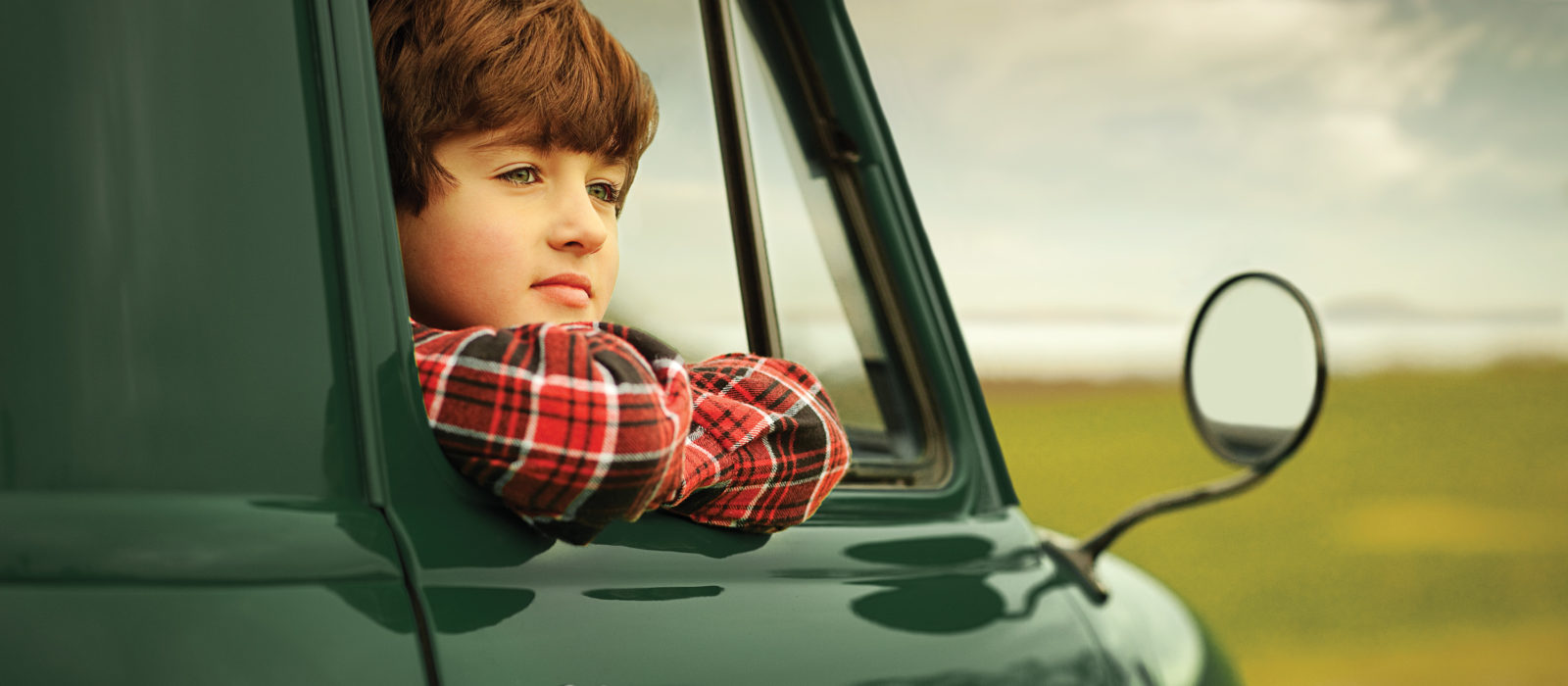 Boy in red plaid shirt looking out the American AgCredit truck window