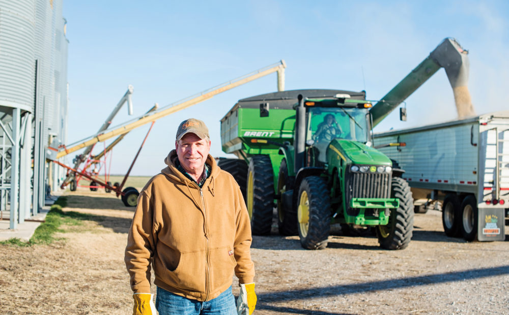 farmer standing in front of farm equipment and silo