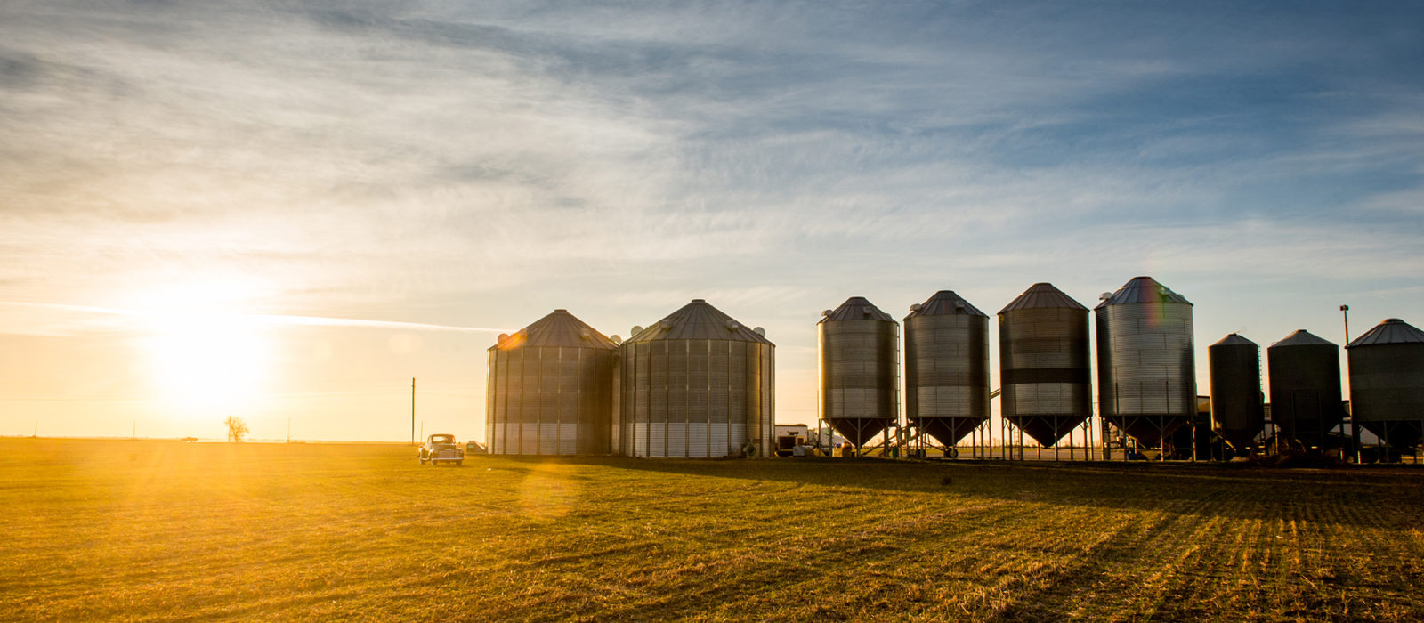 American AgCredit truck from a distance in front of silos at sunset