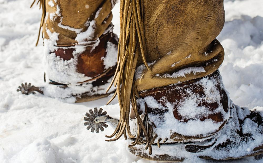 detail of ranchers boots with spurs in the snow