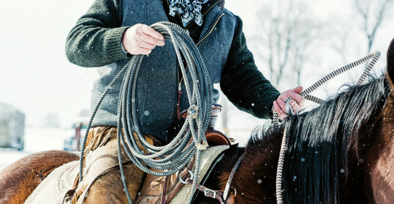 closeup of rancher on horseback with also in the snow