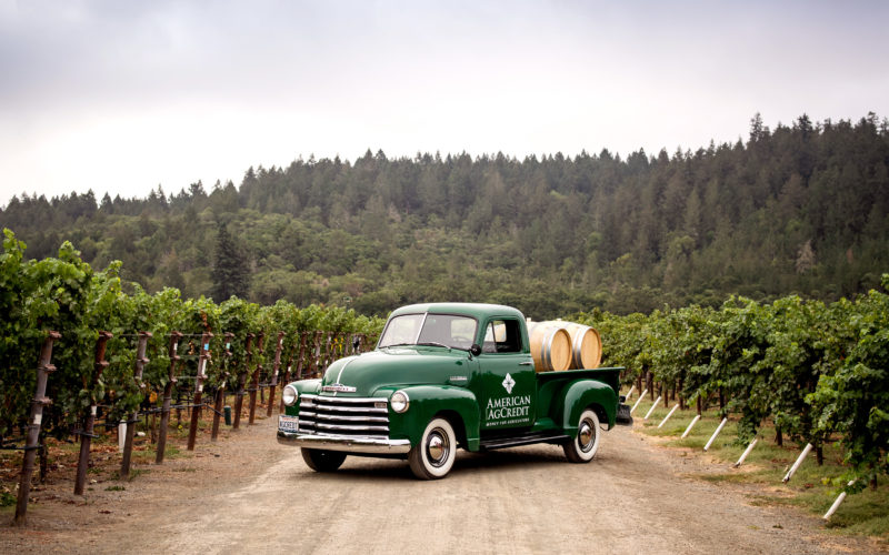 American AgCredit truck with wine barrels in vineyard